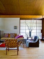 Wooden chair and armchair next to comfortable sofa with cushions in front of sliding wall element covered in Japanese paper in modern interior with wood-clad, barrel-vaulted ceiling
