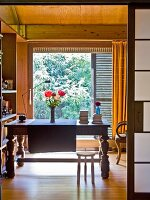 View though open sliding door of antique wooden table in front of floor-to-ceiling window in wood-panelled room with garden view