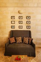 Dark brown armchair with ethic scatter cushions below collection of framed butterflies on stone wall
