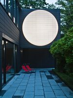 Residential extension with large, white circular area in dark facade at twilight; loungers with red covers on terrace