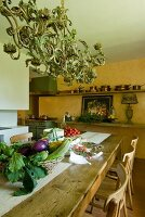 Fresh vegetables on long table in Mediterranean kitchen-dining room; pretty pendant lamp above table and still-life painting on apricot wall