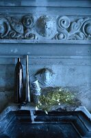 Stone basin, mirrored vases, beakers and Christmas decorations below antique, Greek-style stucco elements
