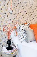 Hen-patterned wallpaper and pillow behind Easter eggs hanging from orange ribbons