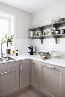 Kitchen base units with modern panelled fronts and open shelving in shades of grey, white work surfaces and wall tiles