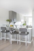 Breakfast bar with upholstered stools in white and grey, open-plan kitchen