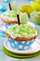 Apple muffins decorated as apples with icing, green sprinkles, chocolate sticks and leaf-shaped sweets