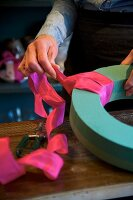 Hands of woman creating wreath of flowers using oasis foam and deep pink silk ribbon