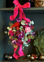 Spherical flower arrangement with roses tied to shelf with silk ribbon