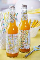 Bottles decorated for party - sleeves and flower-shapes cut from old maps