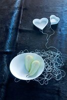 Unconventional decorative idea for wedding banquet - white threads connecting dish with two pear halves and heart-shaped dishes on dark, animal-skin blanket