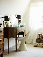 White shell chair in front of antique dressing table in dark wood next to window with curtain