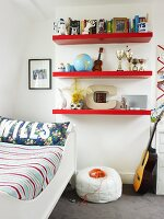 Red floating shelves, white sleigh bed, pouffe and guitar in cheerful teenager's bedroom