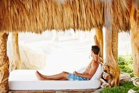 Man wearing shorts relaxing on wide mattress under palm leaf roof