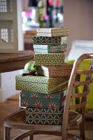 Stack of boxes in retro patterns on wooden Thonet chair