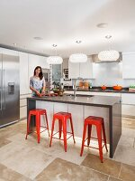 Designer kitchen with island counter and red bar stools; young woman preparing vegetables at counter