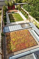 View of property; view down onto green roof with skylights and garden with small trees and lawn