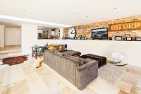 Extended, open-plan, modern living area with exposed brickwork, stone flagged floor and view into raised kitchen