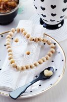 Wire love-heart threaded with wooden beads and linen napkin next to spoon on plate
