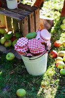 Vintage wooden crate of harvested apples and preserving jars with red and white fabric covers in enamel bucket