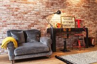 Couch with grey upholstery next to black metal table and vintage swivel chairs against illuminated brick wall