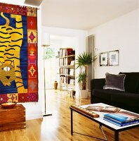 Ethnic wall hanging on wall opposite coffee table and black sofa in open-plan interior