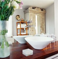 Washbasin on wooden counter in front of mirror reflecting vintage cupboard and wooden shelves