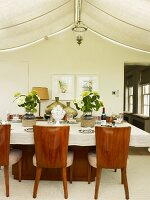 Elegant walnut chairs with upholstered seats at set dining table below awnings in conservatory