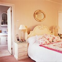 Floral scatter cushions and bedspread on bed with curved headboard next to bathroom door