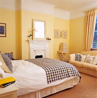 Pleasant bedroom with yellow-painted walls and checked textiles on bed and sofa