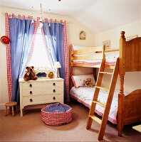 Nostalgic children's bedroom with wooden, country-house-style bunk beds and red gingham trim on various textiles