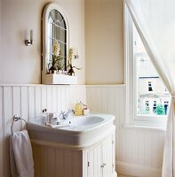 Mirror resting on dado rail of white wooden panelling above sink in elegant, country-house-style bathroom