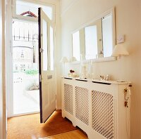 Elegant hallway with mirror on wall and skilfully crafted radiator cover behind open front door