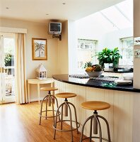 Curved kitchen counter and bar stools; wall-mounted TV below ceiling