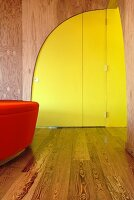 Modern, curved, yellow interior door in wooden wall of foyer