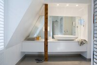 Washstand with incorporated wooden pillar below sloping ceiling; spotlights on ceiling above large, counter-top washbasin in front of mirrored wall