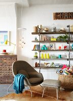 Grey designer armchair with footstool on cowhide rug, basket of cushions and colourful ornaments on shelves against wall; antique apothecary cabinet in background