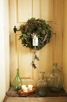 Festive wreath on vintage interior door and collection of glass bottles on floor in door niche