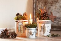 Christmas arrangement with lit candle in tin can with star motif