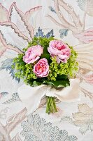 Small bridal bouquet of lady's mantle and roses on patterned surface