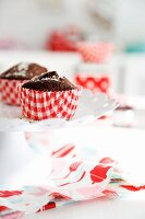 Chocolate muffins in red and white paper cases on white tabletop