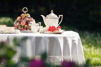 Garden table romantically set with white tablecloth, gold-rimmed tea service and opulent cake stand decorated with flowers