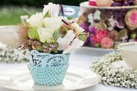 Romantic arrangement of flowers and place card on garden table set for festive afternoon tea party