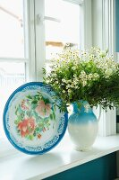 Floral decorative plate next to bouquet of chamomile in pale blue jug on sill of lattice window