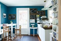 Nostalgic sales room with bistro stools, white counter table and blackboards on blue walls; country-house ambiance