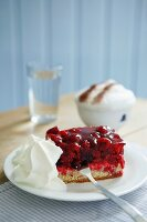 Slice of cherry cake and cream on white plate and blue and white checked napkin