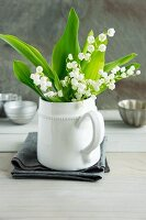 Posy of lily of the valley in white china jug