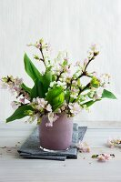 Flowering twigs and lily of the valley in pink glass vase