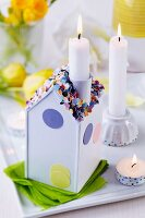 Lit candle in chimney of house-shaped candlestick decorated with confetti