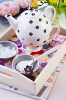 Polka-dot teapot and cup set on tray decorated with confetti