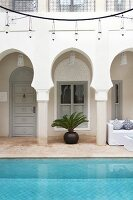 Arcade & pool below circular rack of lamps in courtyard of Moroccan house